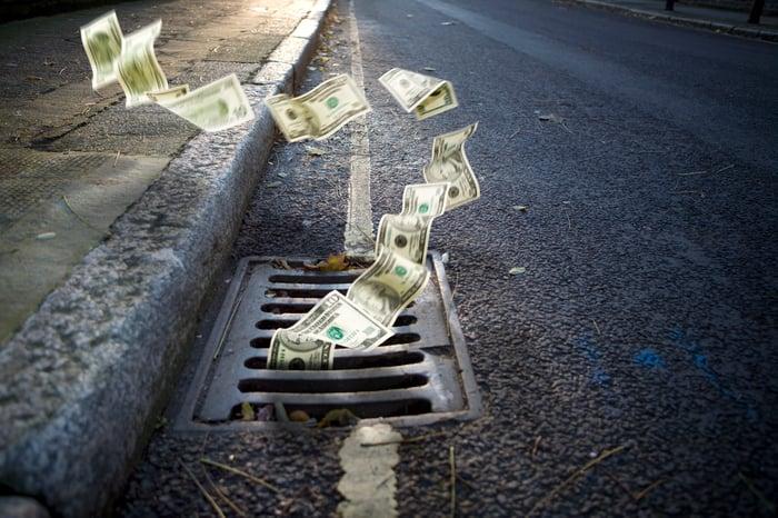 L'argent tombe dans un drain.