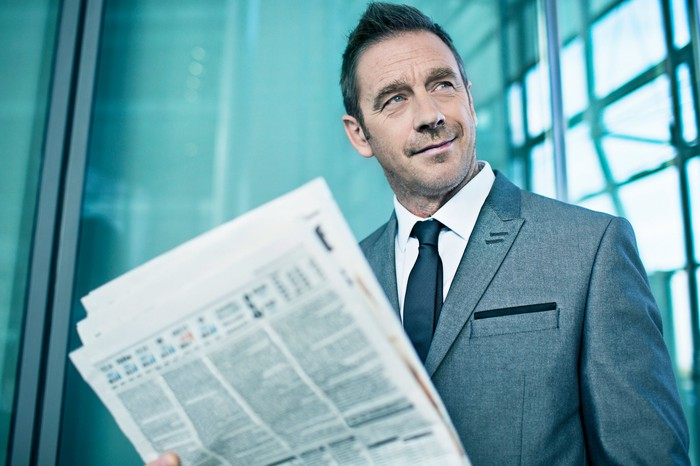 A businessman in a suit holding a financial newspaper while looking off to his left.