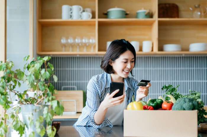 Woman smiling while holding mobile phone and credit card with box of groceries nearby