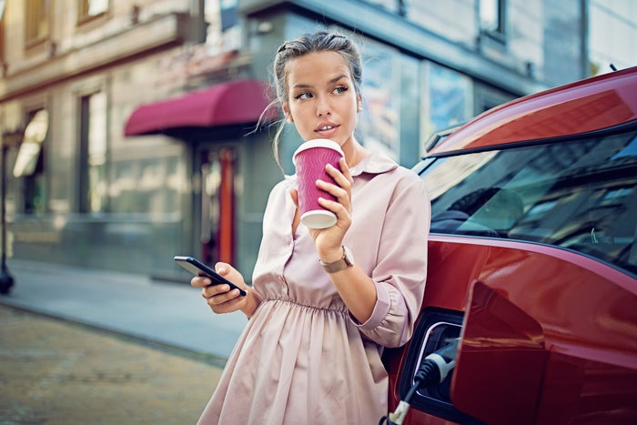A woman drinking a beverage and looking at her phone leans against an electric vehicle while it charges.