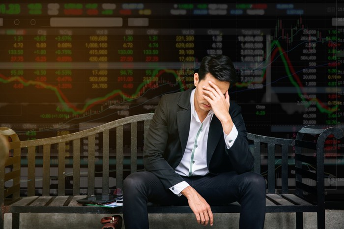 Illustration of a despondent man in front of stock charts.