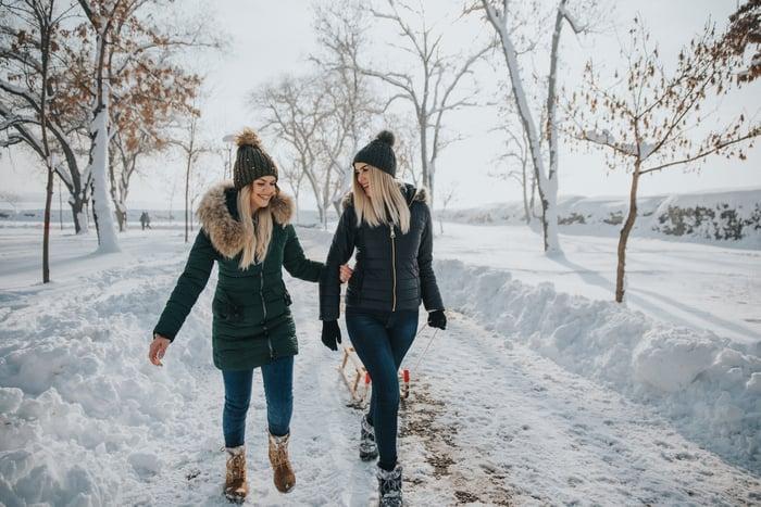 Two women wearing parkas walk down a snowy lane.