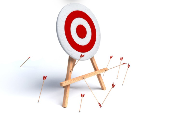 A target with arrows stuck in the ground and the stand holding the target
