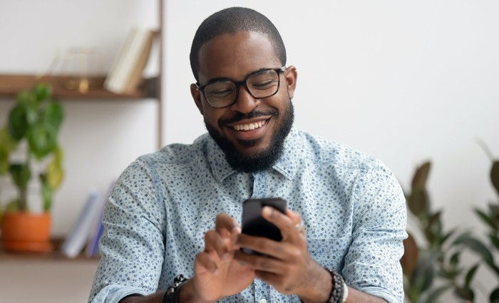 Man smiling while looking at his phone