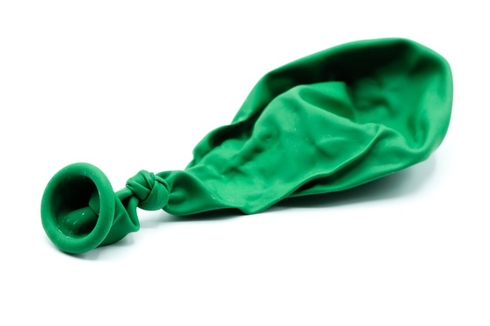 Deflated green balloon on a white background