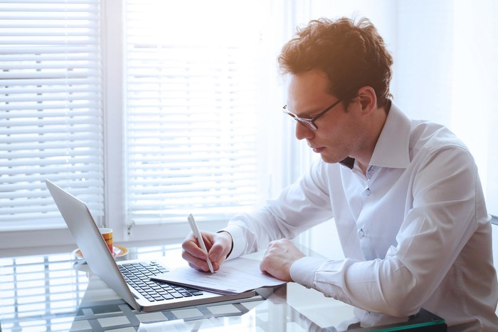 Man sitting at a laptop taking notes on a pad of paper