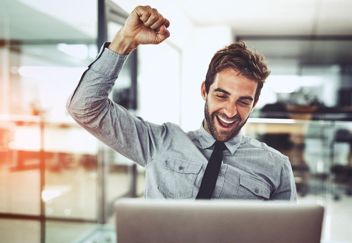 Smiling man at laptop raising arm in victory
