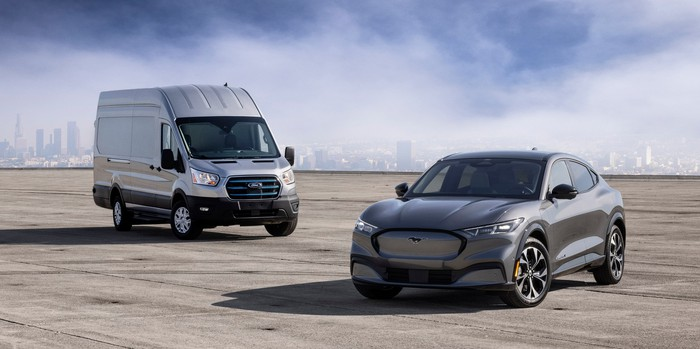 A prototype of Ford's e-Transit, an electric commercial van, with a silver Ford Mustang Mach-E electric crossover.
