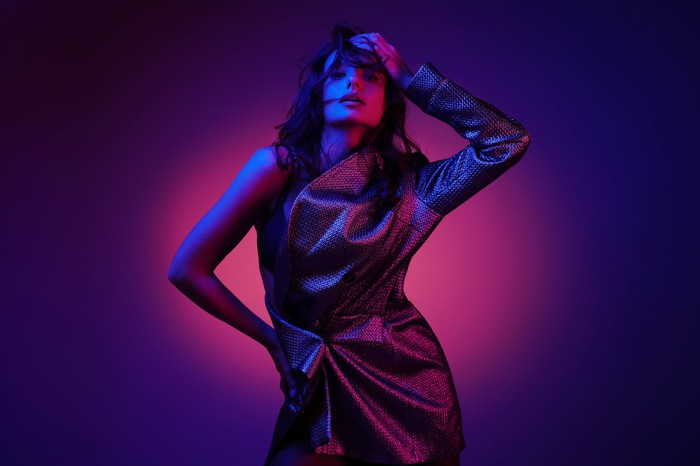 Fashion model in stylish clothing with neon lights in studio.