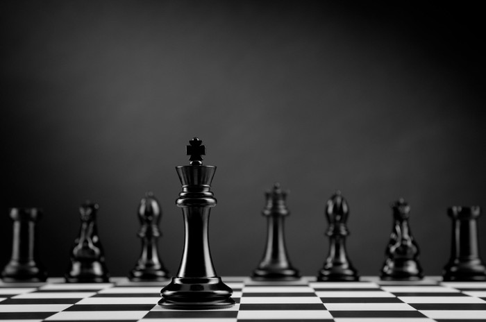 Pieces on a chessboard with the king in the front.