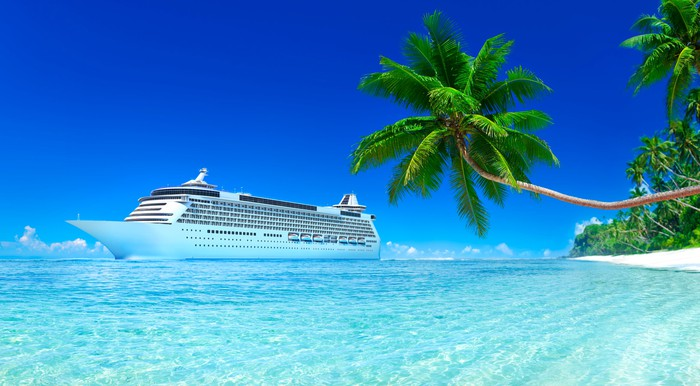 Cruise liner sailing through crystal clear waters with a coconut tree in the foreground