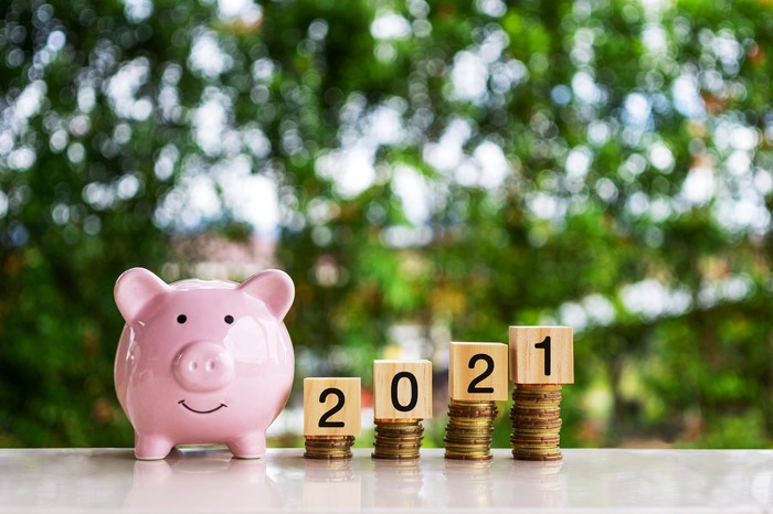 A smiling piggy bank next to rising stacks of coins with blocks atop them spelling out 2021.