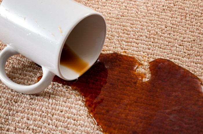 A spilled cup of coffee soaking into a carpet.