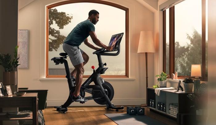 Homme monté sur un vélo Peloton + à la maison