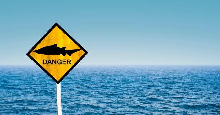 Océan avec panneau disant Danger avec une photo d'un requin.