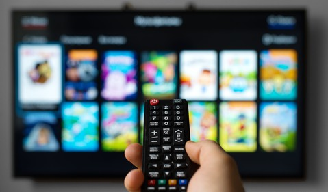 Man pointing remote at a TV