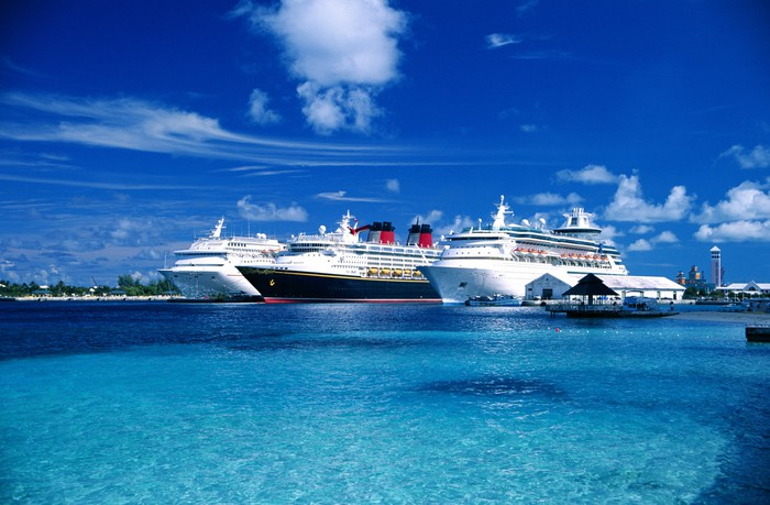 Three cruise ships parked adjacent to one another in clear blue waters.