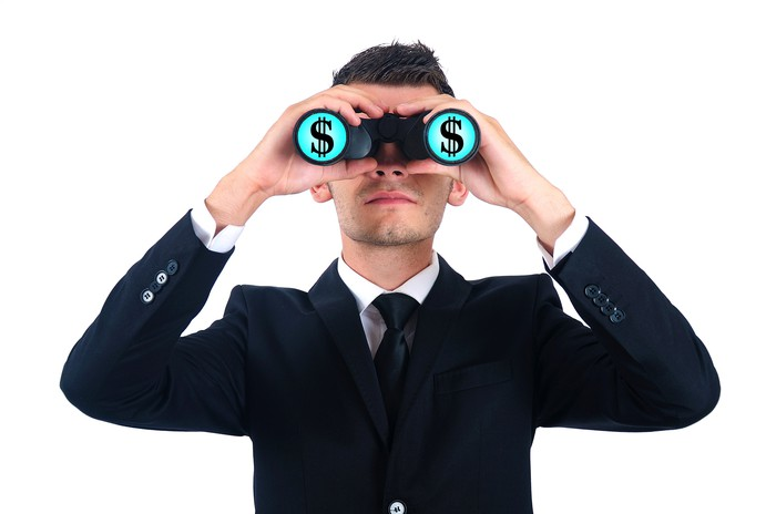Man wearing a coat and a tie holding binoculars with dollar signs in each lens