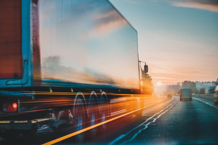 A truck driving on a highway at sunset.