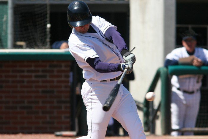 Baseball batter hitting a pitch.