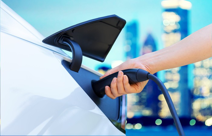 Closeup of a hand inserting a charger into an electric vehicle.