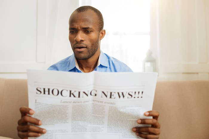 A man reads a newspaper with a front page headline of shocking news.