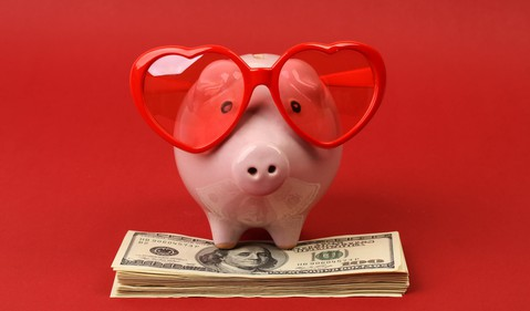 piggy bank wearing heart glasses on top of a stack of money