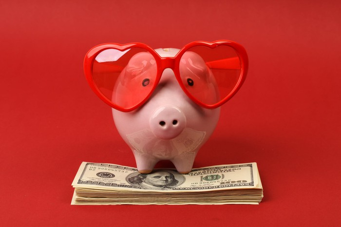 Piggy bank wearing heart glasses on top of a pile of money