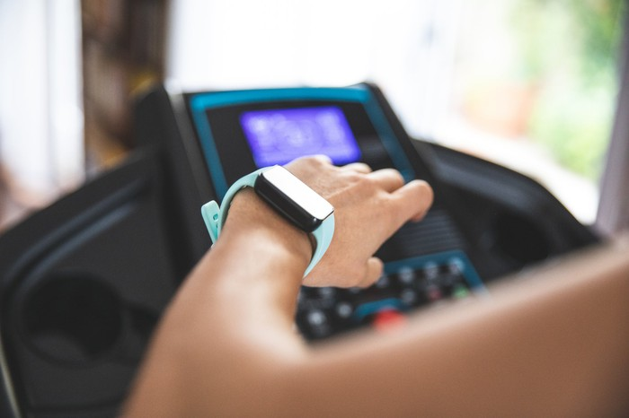 A woman looking at her watch on her wrist while using a treadmill.
