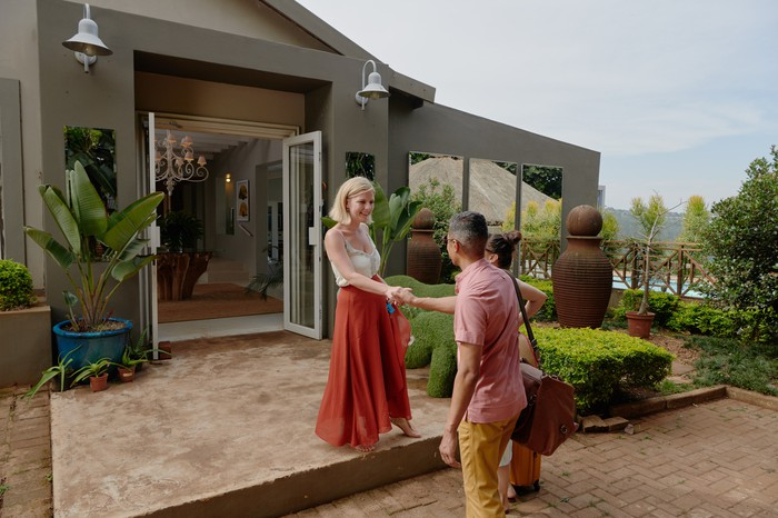 An Airbnb host greets their guest upon arrival.