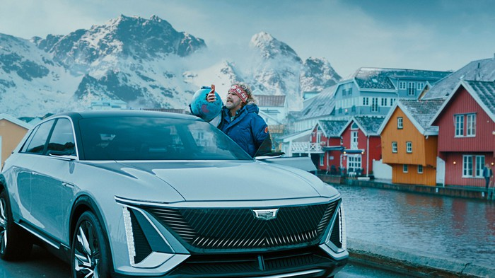 The actor Will Ferrell, with a Cadillac Lyriq in a Norwegian town.
