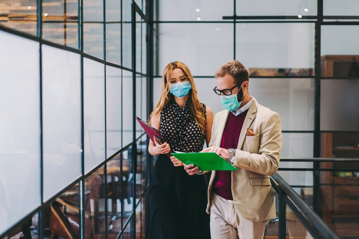 Masked man and  woman in an office looking at documents