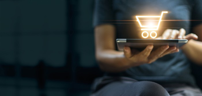 A person holding a tablet displaying a glowing shopping-cart icon.