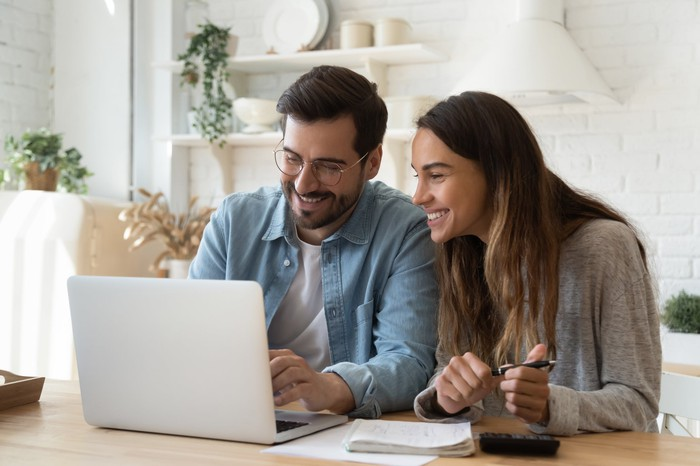 Happy couple looking at their investment account  on a laptop.