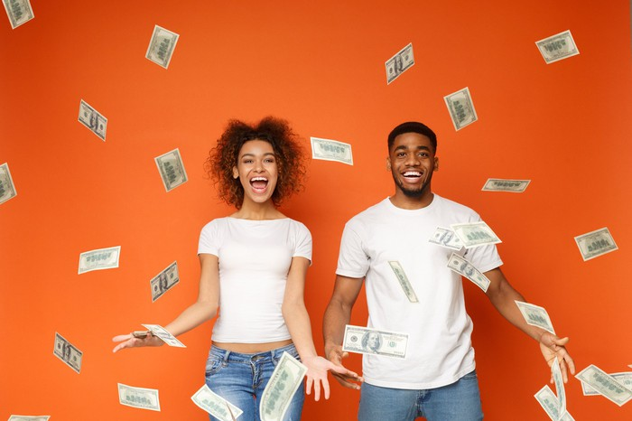 Couple smiling and throwing cash in the air, against orange background.