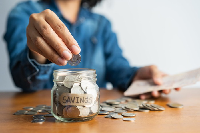 Woman putting coins in a jar labeled Savings