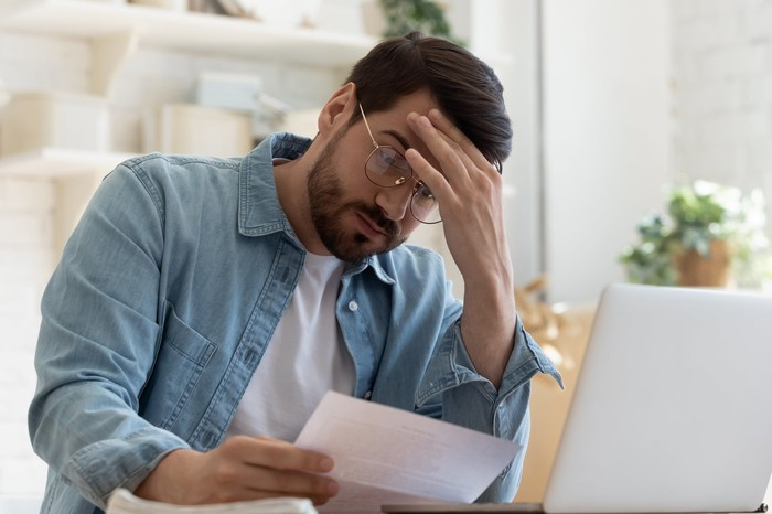 Man at laptop holding head while reading document