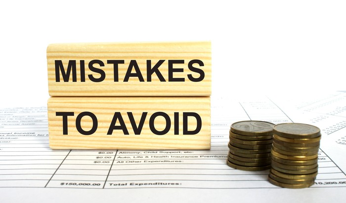 A sign that says mistakes to avoid next to two piles of coins.