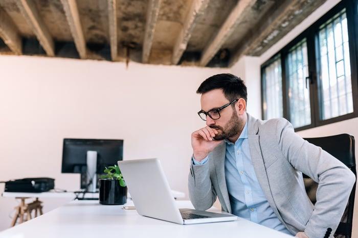 Jeune homme assis à un bureau en regardant un ordinateur portable