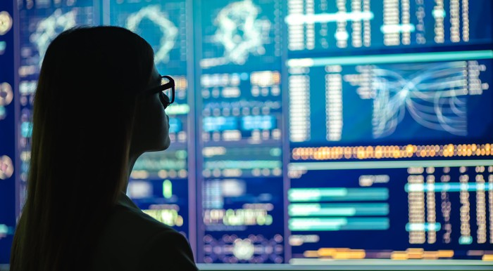 A woman looking at a giant screen filled with indexes and graphs