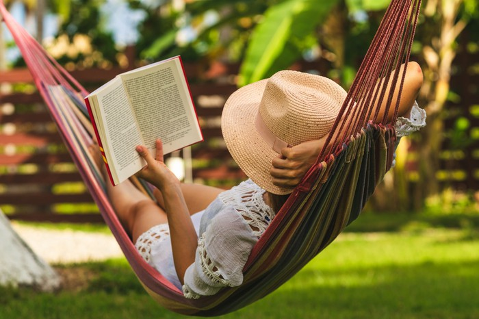 A person reading a book while lying in a hammock.