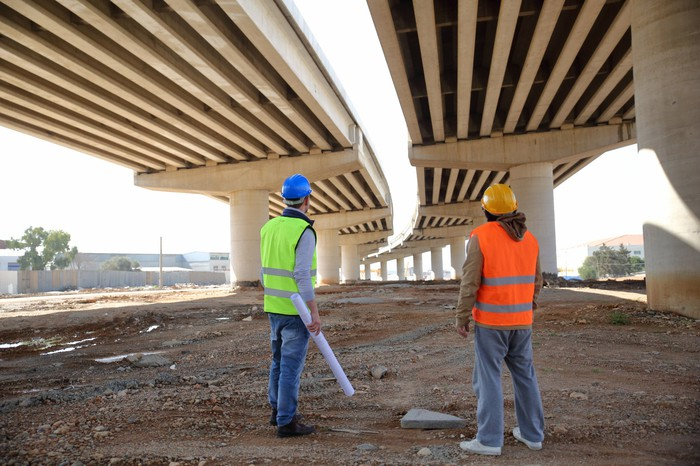 Two workers stand underneath a highway project.