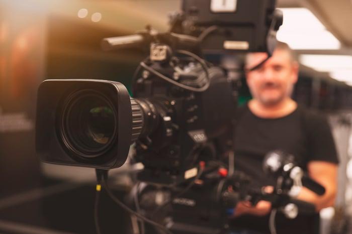 A cameraman sitting behind a TV production camera.