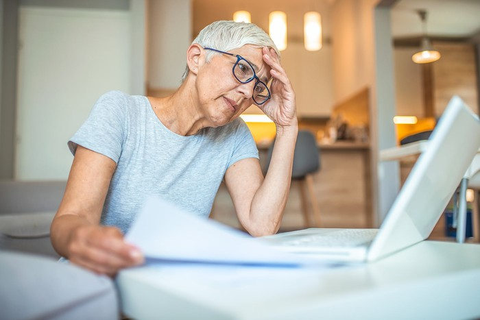 Older person at laptop holding head with one hand and document with another.