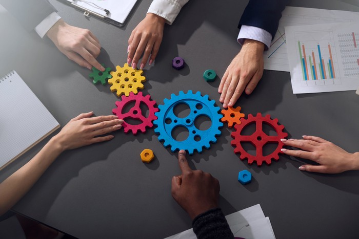 A set of colored cog wheels sitting on a table, with business people interacting with them.