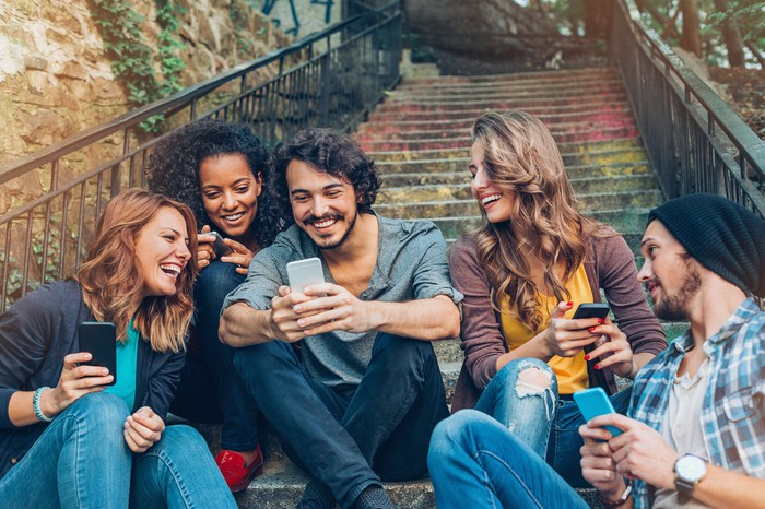 A group of young adults sitting on stairs outside looking at their cellphones.