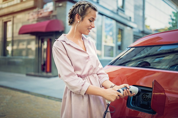 A woman charges an electric car