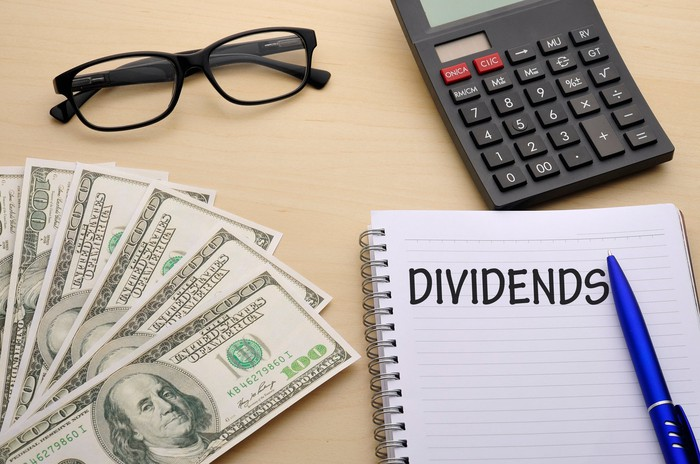 Cash, glasses, calculator, pen, and notebook with word Dividends written in it, all on a table.