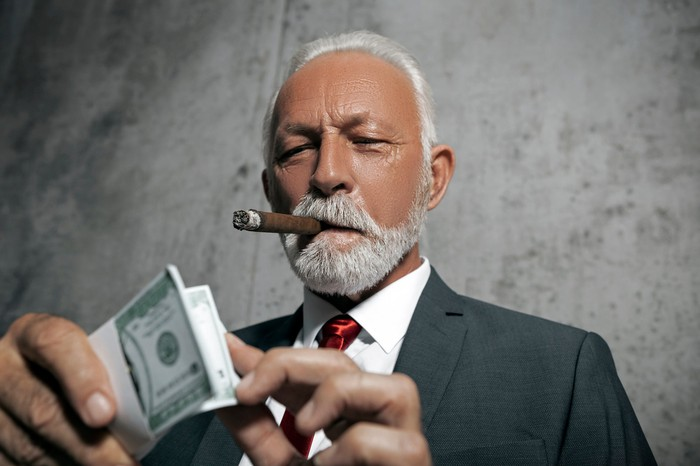 Man in suit with cigar  counting wad of bills