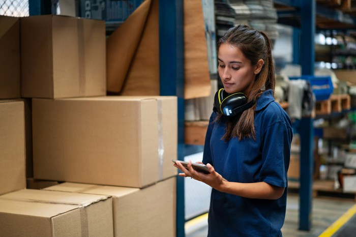 A warehouse worker monitors inventory on a tablet.